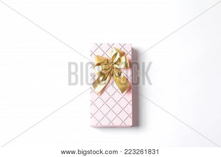 Pink gift box with a large gold bow. White background. Holiday concept, flat lay, top view