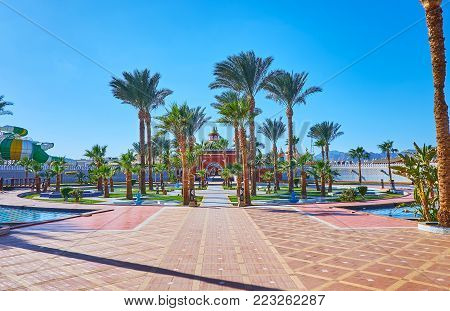 The small palm garden with fountains in front of the entrance to Alf leila wa leila palace (1001 nights), Sharm El Sheikh, Egypt.