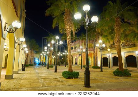 The scenic shopping street with European architecture, alley of palm trees and bright old-fashioned streetlights, Sharm El Sheikh, Egypt.