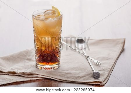Invigorating cocktail with an ice cube and a slice of lemon on a beige napkin