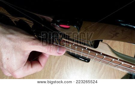Playing an electric guitar with a large screen the correct setting of the hands and fingers of a black stratocaster