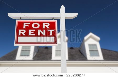 Left Facing For Rent Real Estate Sign In Front of House and Deep Blue Sky.