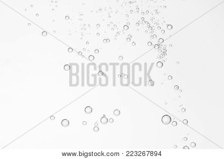 Many small air bubbles soars over a light background.