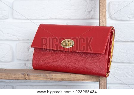 Red woman s leather clutch laying on the wooden shelf on white wall background in the shop. Perfect for everyday casual look and for pretty cocktail dress.
