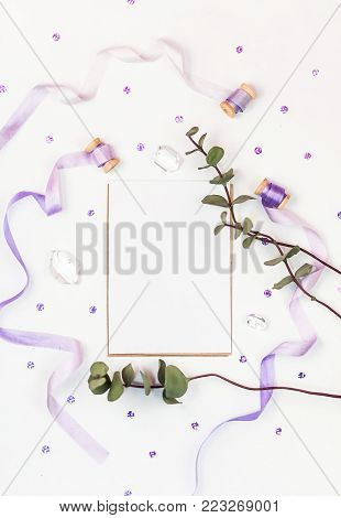 Bright composition with silk ribbons, eucalyptus, sequins and crystal on a white background. Space for a greeting text. Photos for social media, blogs and web sites. Flat lay, top view