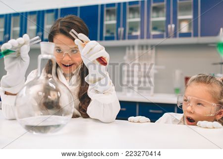 Two little kids in lab coat learning chemistry in school laboratory. Studying ingredients for experiments . Young scientists in protective glasses making experiment in lab or chemical cabinet. Dangerous Experiments