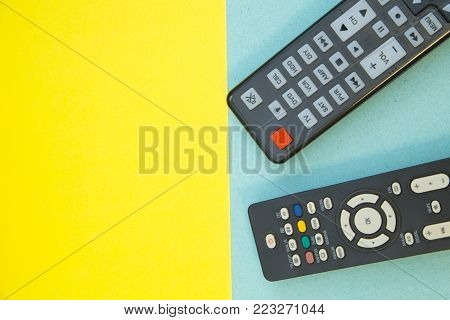 Weekend, Leisure, Lifestyle Concept. Weekend with family, two remote controls on a light blue and yellow background, flat lay
