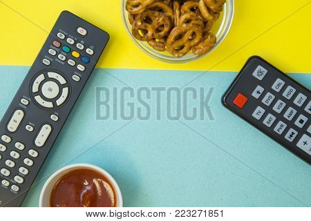 Weekend, Leisure, Lifestyle Concept. Weekend with family, two remote controls, salty pretzels and ketchup on a light blue and yellow background, flat lay