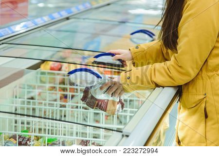 woman get products from the fridge in supermarket