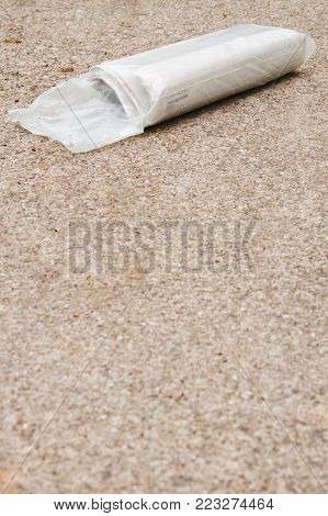 A newspaper package delivery on driveway with nobody.