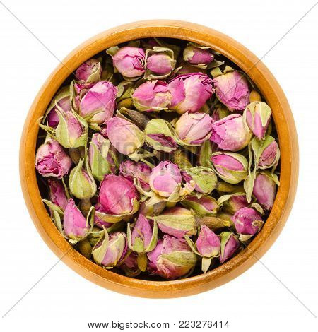 Dried rose buds in wooden bowl. Flowering plant of the genus Rosa. Used as decoration, as scent, for teas and perfums. Isolated macro food photo close up from above on white background.