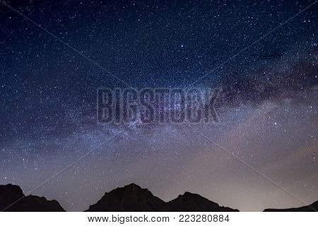 The wonderful starry sky on Christmas time and the majestic high mountain range of the Italian Alps.