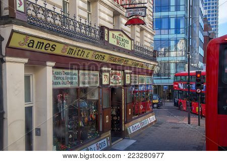 LONDON, UK - NOVEMBER 28, 2017: Small workshop and traditional umbrella shop, founded in 1830 but still functional. Double-Decker red buses on the street, typical for London. James Smith & Sons.