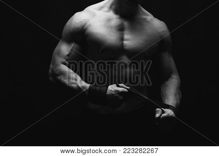 Strong athletic man, bodybuilder. Unrecognizable, no face portrait. Naked torso, muscular body. Strong chest and shoulder muscles. Studio shot on black background, low key, black and white image