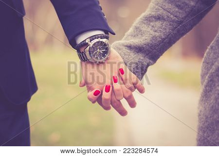 Couple in love holding hands in park outdoor. A man wearing elegant wrist watch. Close up.