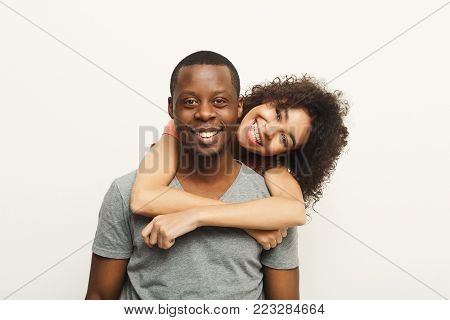 Studio shot of happy casual african-american couple embracing, posing to camera and smiling on white studio background, copy space, isolated