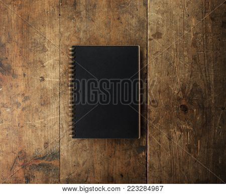 Black cover and gold spiral coil notebook isolated on rustic wooden table with plenty of copy space.
