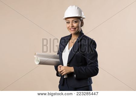 Young architect engineer woman wearing helmet isolated on studio background