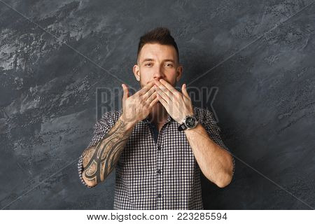 Keeping silence or blowing a kiss. Man holding covering mouth with both hands against grey studio background, copy space