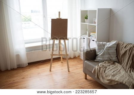 fine art, creativity and artistic tools concept - wooden easel at home room or studio