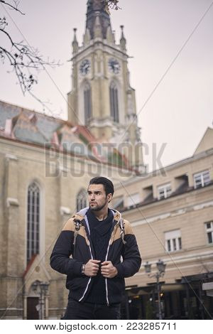 one young man, upper body shot. Cathedral, European old vintage architecture behind. Location