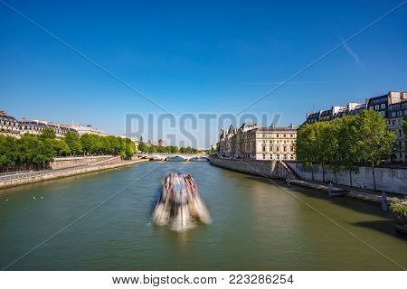 Wide angle long exposure view of blurred tourist boat over Seine river, Paris
