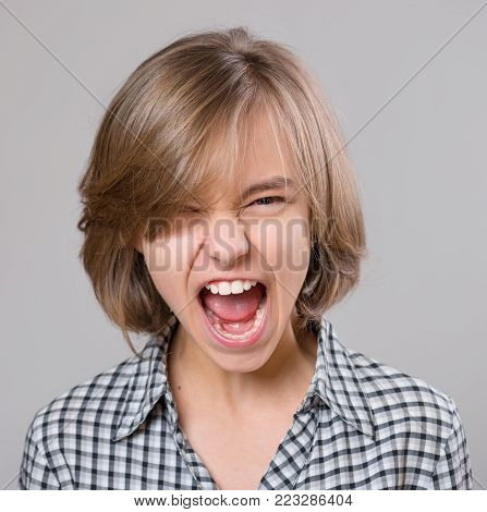 Close-up emotional portrait of attractive angry child teenager girl screaming wide open mouth. Funny cute child on gray background. Negative human face expression. Conflict concept.