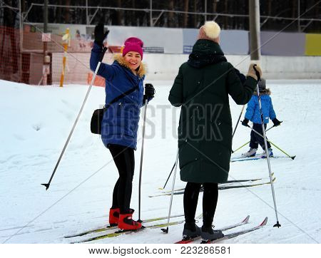 Two young beautiful girls go skiing in winter on a ski slope.