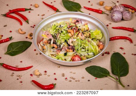 Salad of cashew nuts and lettuce at the background of the chilli pepper, cashew nuts and green leaves