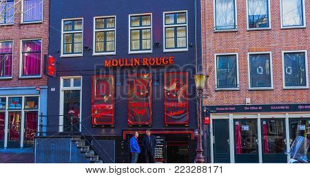 Amsterdam, Netherlands - December 14, 2017: Red Light District at night. It is probably the world's most famous in its kind. There are over 500 windows in the Amsterdam Red Light District and about 1000 working girls.