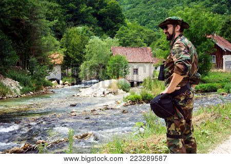 The smiling man in military uniform is standing at riverside outdoors in nature on rural scene.