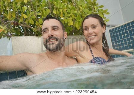 Couple relaxing in jacuzzi pool