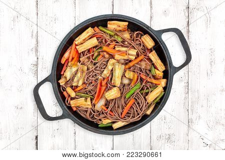 Delicious buckwheat noodles with tofu skin and vegetables in a cast iron wok on light wooden background, top view