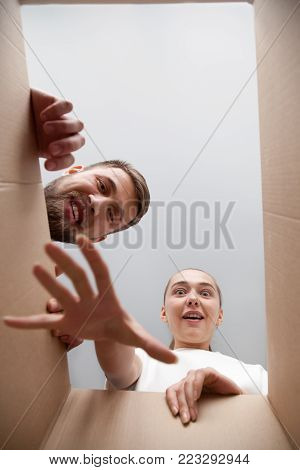 Young surprised couple looking inside open cardboard box, impatient cute woman reaching hand eager to take present gift order out of carton package while man peeking, parcel delivery service concept