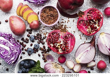 Vegetables and fruits with anthocyanin purple and pink: red cabbage, onion, pomegranate, blueberries, rice, apples, potatoes, garlic beans, radish for healthy nutrition. Top view. Color of the year violet