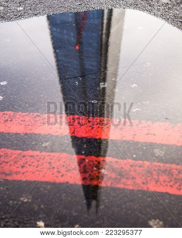 Reflection of the Shard in London in a puddle