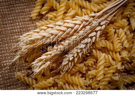 Bread spikes and pasta on rough fabric background