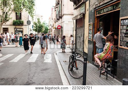 BARCELONA, SPAIN - AUGUST 16, 2017:  Cozy street in Barcelona with bar, bike and girl sitting outdoor on a chair near the cafe and relaxing people at summer day. Barcelona is one of the most famous and fun cities  in Europe