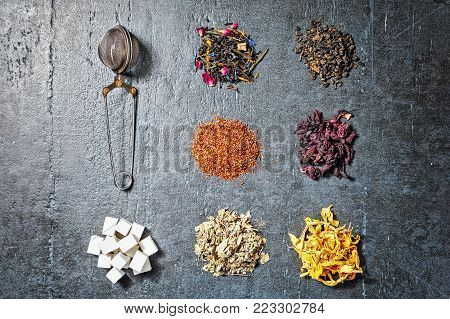 Aromatic flower tea in spoon on rustic black background, top view.