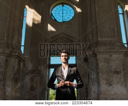 Handsome groom waiting for the bride on the background of beautiful architecture. Rich groom on the wedding day. Elegant groom in a black suit . Wedding day