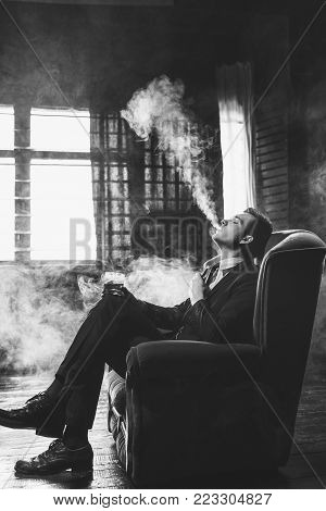 Man vaping fumes and drinking alcohol to relax. Enjoyment satisfaction and chilling concept