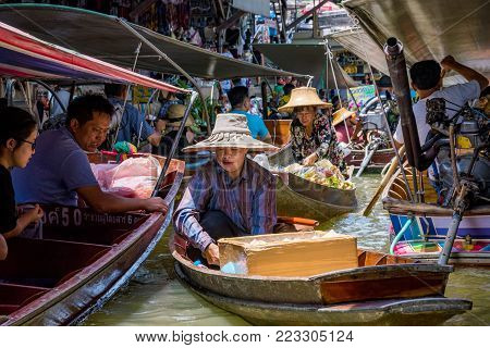 RATCHABURI, THAILAND - AUGUST 14: This is a boat seller selling coconut drinks to people in the famous Damnoen Saduak floating market on August 14, 2017 in Ratchaburi