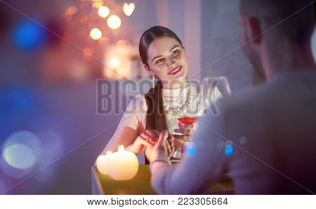 Romantic dinner. Young couple Toasting Wine Glass In restaurant or at home, holding hands, love Dating. Beautiful brunette woman on romantic dinner drinking at bar. Date. Valentines Day celebrating.