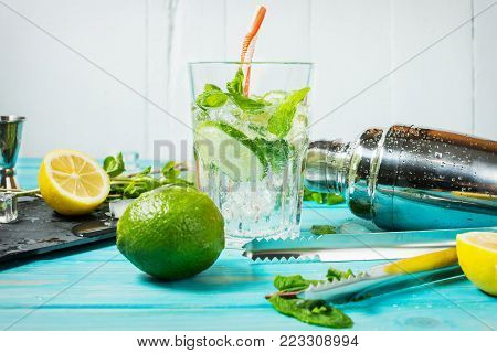 Mojito cocktail with lime and mint in highball glass on a blue wood table. Drink making tools and ingredients for cocktail.