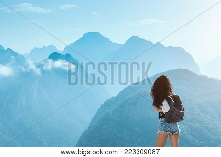 Hipster young girl with backpack enjoying sunset on peak of mountain. Tourist traveler on blue background valley landscape view mockup for text. Attractive slim brunette mixed race Asian Caucasian woman againts beautiful travel copy space background. Back
