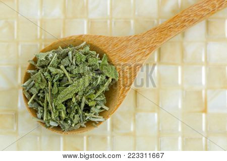 Closeup of Dried Sage leaves to make herbal tea in wooden spoon, top view, on yellow tile background (salvia officinalis)