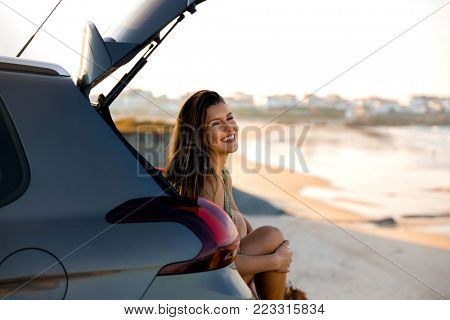 Beautiful woman sitting in the trunk of a car near a beach and smilling