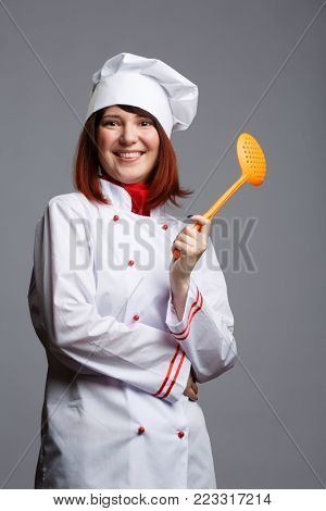 Picture woman cooks in white robe and cap with slotted spoon in hand
