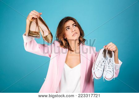 Portrait of a pensive woman dressed in pink suit holding pair of high heels shoes and pair of sneakers isolated over blue background