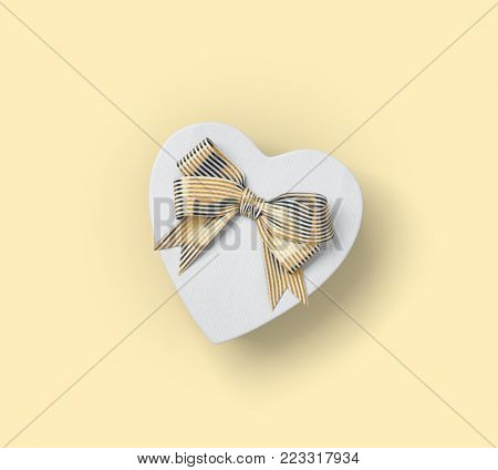 Heart shaped gift box with golden bow. Top view